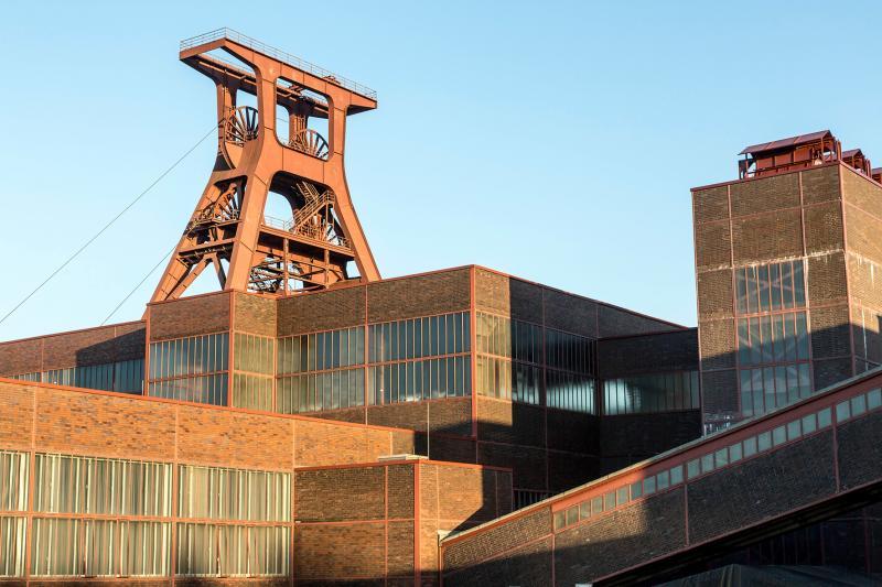 """Die Zentralschachtanlage Zollverein XII wurde 1932 in Betrieb genommen und zählte bis zu ihrer Stilllegung 1986 zu den größten und leistungsstärksten Steinkohlenzechen weltweit. Das Meisterwerk der Bergbauarchitektur, geschaffen von den Visionären Fritz Schupp und Martin Kremmer, galt von Beginn an als """"schönste Zeche der Welt""""."""