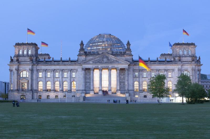 Blick vom Platz der Republik auf das beleuchtete Reichstagsgebäude in der Dämmerung, 2014.