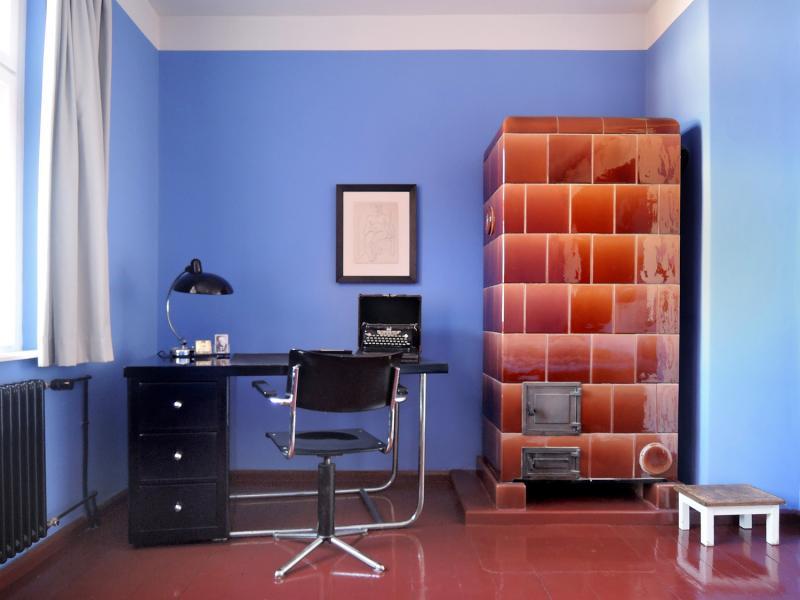 Tautes Heim, Berlin: Arbeitsecke im Schlafzimmer mit historischem Kachelofen und Porträt des Architekten, 2012.