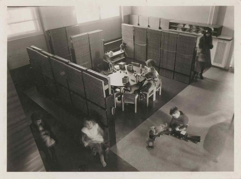 Städtischer Kindergarten Goethehof, Wien II, Schüttaustraße, Innenansichten: Beschäftigungsraum mit Kindern am Tisch. Die Schlafpritschen sind hoch gestellt, Entwurf: Franz Singer, Mitarbeit: Friedl Dicker, Foto: Pfitzner-Haus, 1932.